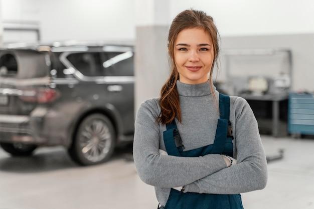 Smileyvrouw die bij een autodienst werkt Gratis Foto