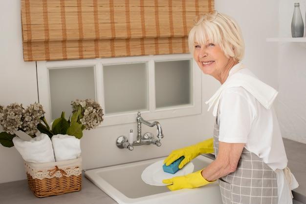 Smileyvrouw die de schotels met handschoenen wassen Gratis Foto