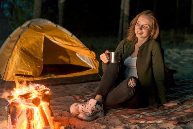 Smileyvrouw die door een kampvuur drinken Gratis Foto