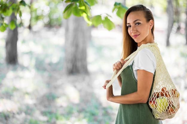 Smileyvrouw die een ecologische zak met exemplaarruimte houdt Premium Foto