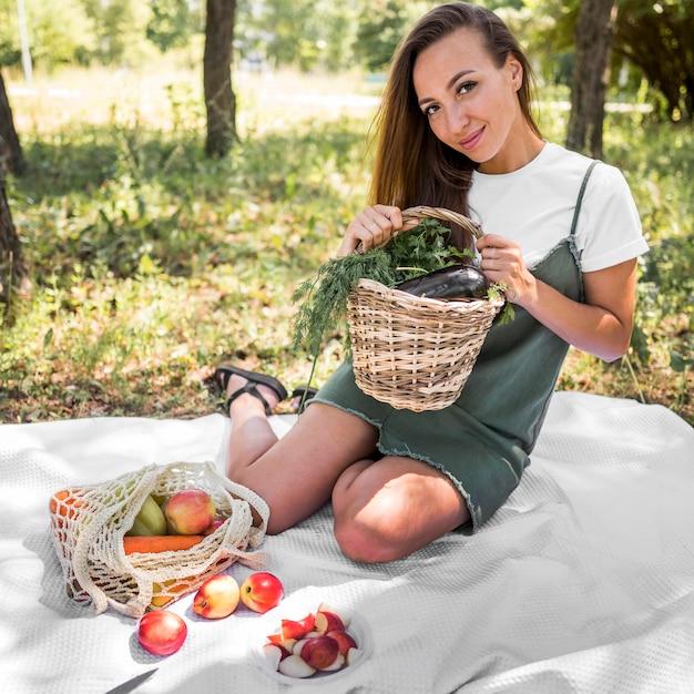 Smileyvrouw die een picknick met gezonde snacks hebben Premium Foto