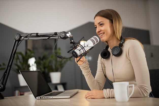 Smileyvrouw die een podcast op de radio met een microfoon en laptop doet Gratis Foto