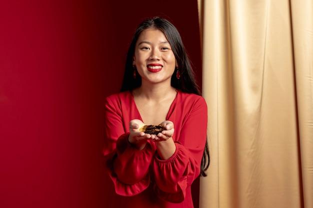Smileyvrouw die gouden confettien in handen houden Gratis Foto