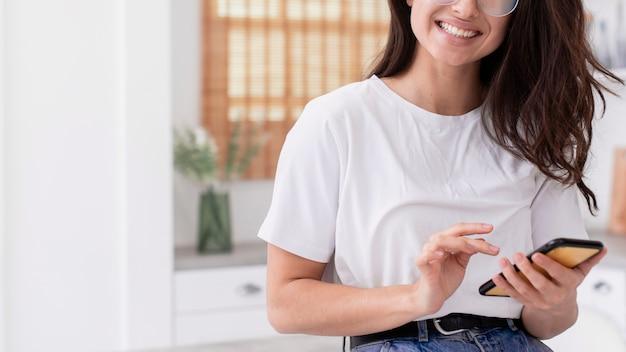 Smileyvrouw die haar telefoon controleert Gratis Foto