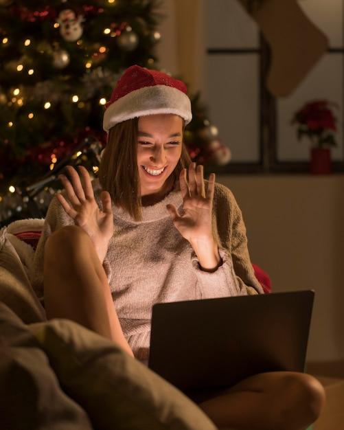 Smileyvrouw die met santahoed laptop bekijkt Gratis Foto