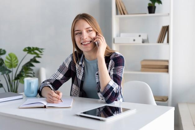 Smileyvrouw die op de telefoon bij haar bureau spreekt Gratis Foto