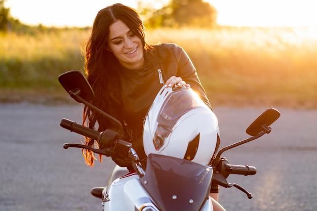 Smileyvrouw die op haar motorfiets rust Gratis Foto