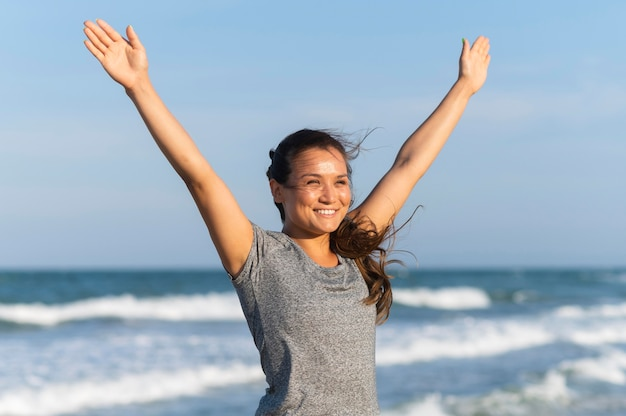 Smileyvrouw die op het strand uitwerkt Gratis Foto