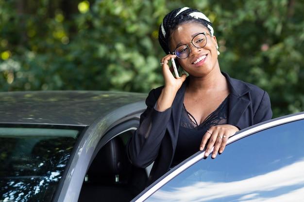 Smileyvrouw die op smartphone spreekt terwijl het krijgen in haar auto Gratis Foto