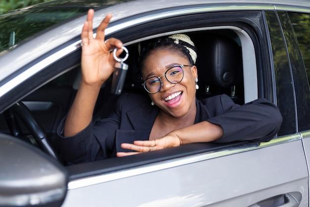 Smileyvrouw die sleutels van haar auto pronkt terwijl zij erin zit Premium Foto