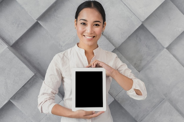 Smileyvrouw die tabletmodel voorstellen Gratis Foto