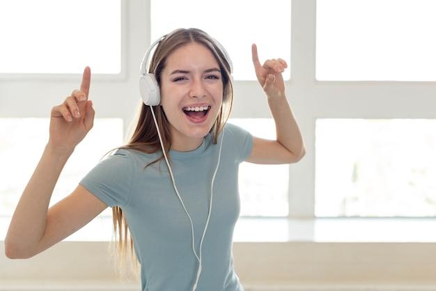Smileyvrouw het luisteren muziek door hoofdtelefoons Gratis Foto