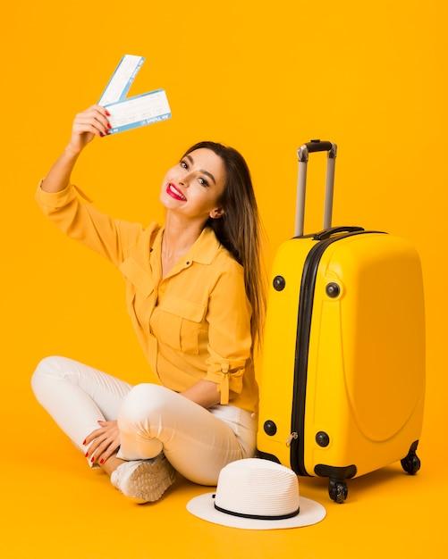 Smileyvrouw het stellen naast bagage terwijl het houden van vliegtuigtickets Gratis Foto