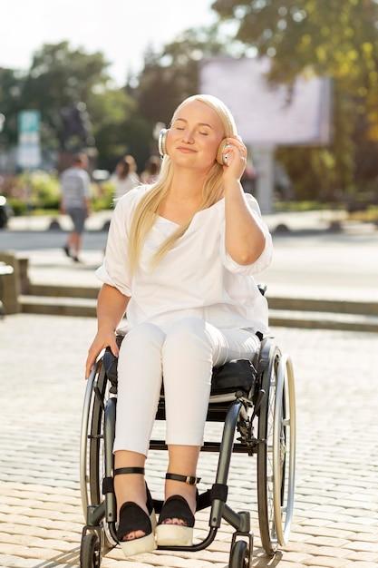 Smileyvrouw in rolstoel die aan muziek op hoofdtelefoons buiten luisteren Gratis Foto