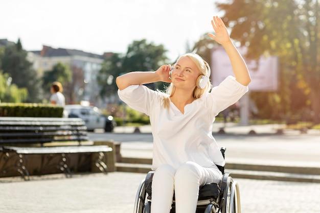 Smileyvrouw in rolstoel die van muziek op hoofdtelefoons genieten Gratis Foto