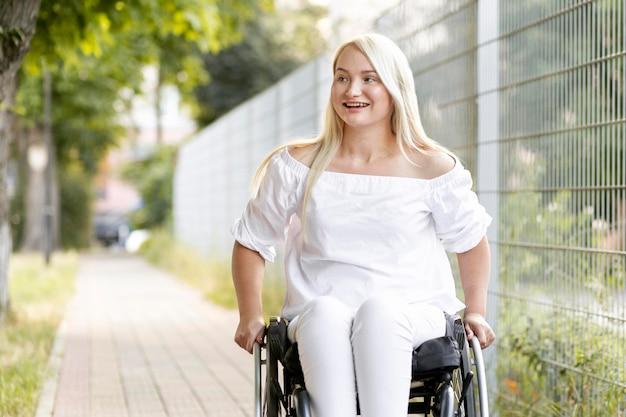 Smileyvrouw in rolstoel in de stad Gratis Foto