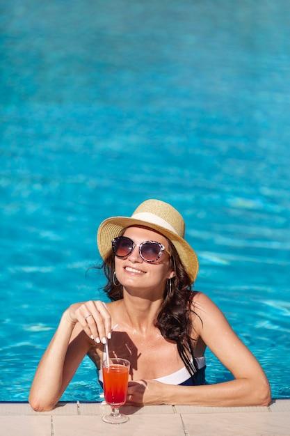 Smileyvrouw met een cocktailzitting in een pool Gratis Foto