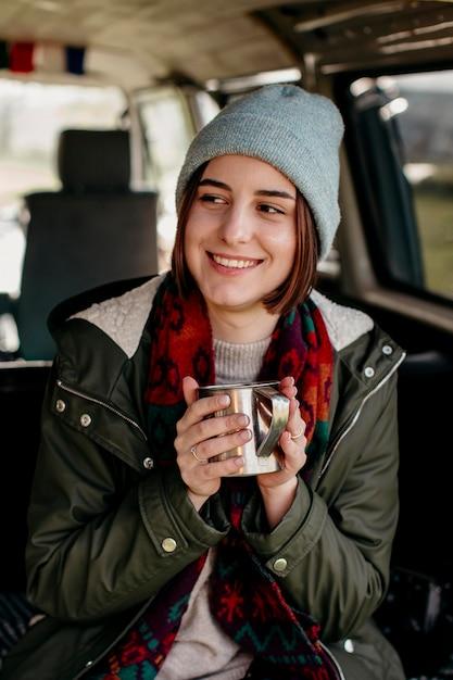 Smileyvrouw met een koffiekopje in een busje Premium Foto