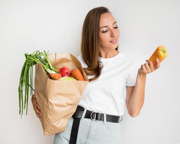 Smileyvrouw met een papieren zak met voedsel Gratis Foto