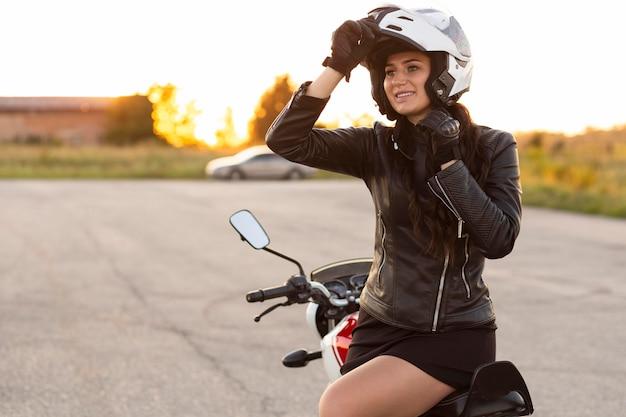 Smileyvrouw met helmzitting op haar motorfiets Gratis Foto