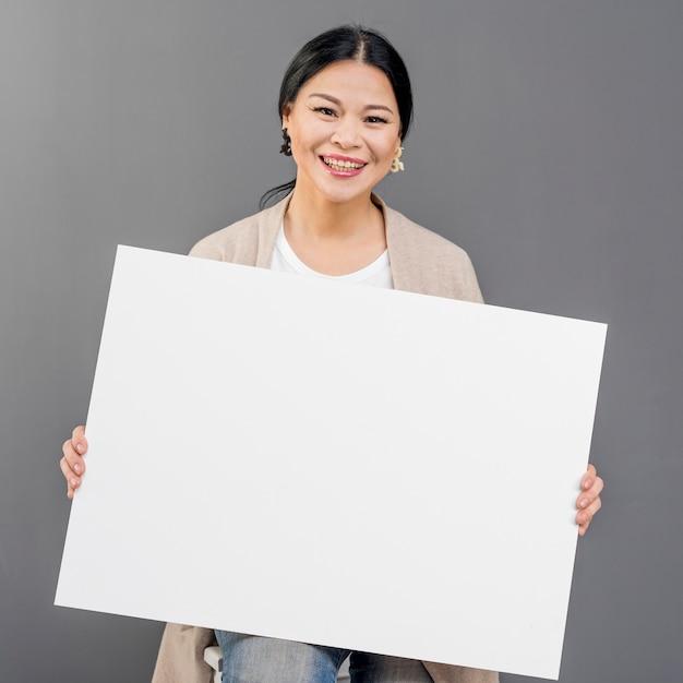 Smileyvrouw met leeg document blad Gratis Foto