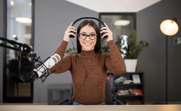 Smileyvrouw op de radio met microfoon en hoofdtelefoons Gratis Foto