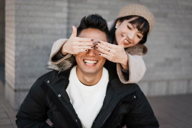 Smileyvrouw verrast haar vriend buitenshuis Gratis Foto