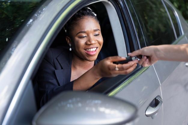 Smileyvrouw wordt de sleutels van haar nieuwe auto overhandigd Gratis Foto