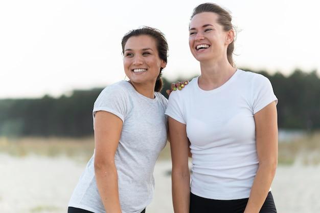 Smileyvrouwen die samen poseren tijdens het trainen op het strand Gratis Foto