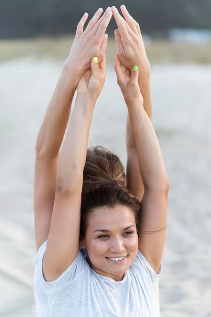 Smileyvrouwen die yoga op het strand doen Gratis Foto