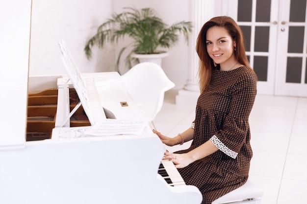 Smilling jonge vrouw zit aan de piano Premium Foto