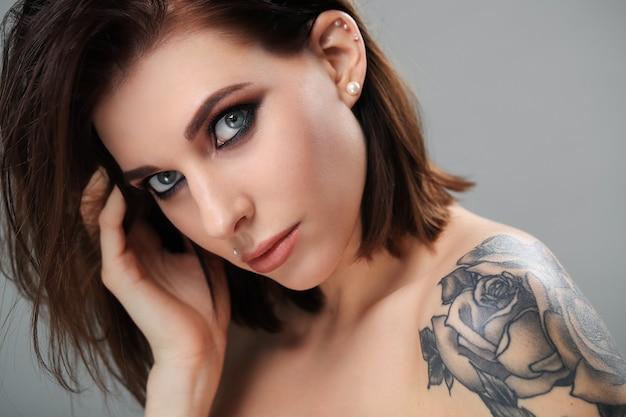 Smokey eye-model met roze tatoeage in de schouder Gratis Foto