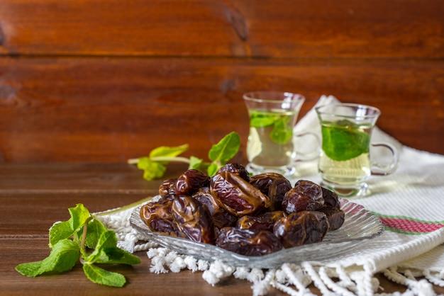 Snack close-up van datums op glazen plaat met mentha thee op achtergrond Premium Foto