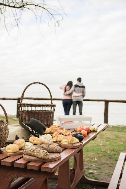 Snack en fruit op picknicktafel met paar op de achtergrond met uitzicht op de zee Gratis Foto