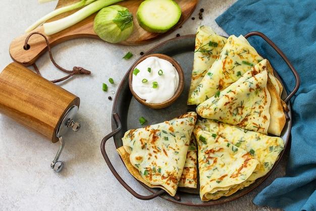 Snack of zomerlunch. courgette pannenkoeken met kruiden geserveerd met zure room in een plaat op een grijze steen of leisteen aanrecht. Premium Foto