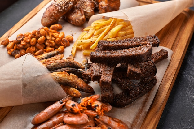 Snack tot bier, op een houten bord. garnalen. gefrituurde vis. gebakken pinda's. patat. kippenvleugels. crunches. croutons. Premium Foto
