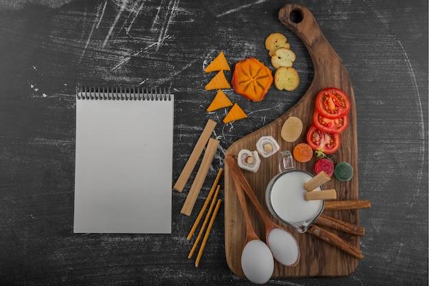 Snackplankje met crackers en groenten met een kookboek apart Gratis Foto