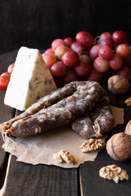 Snacks voor wijn, kaas met schimmel, roze druiven, walnoten en geroosterde droge worst Premium Foto
