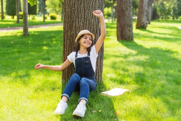 Snak geschoten meisje het stellen voor een boom Gratis Foto