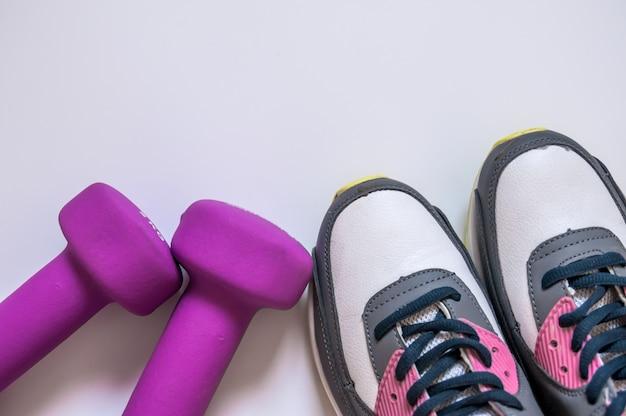 Sneakers en domoren fitness op een witte achtergrond. verschillende hulpmiddelen voor sport. concept gezonde levensstijl, sport en dieet. sportuitrusting. kopieer de ruimte. platte lay-out van fitness en trainings accessoires Gratis Foto