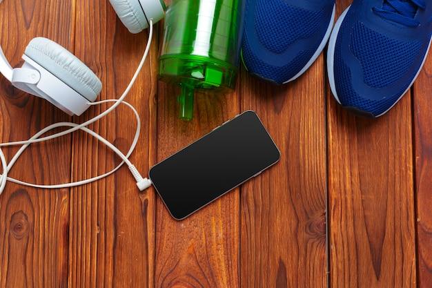 Sneakers en mobiele telefoon met koptelefoon op houten tafel Premium Foto