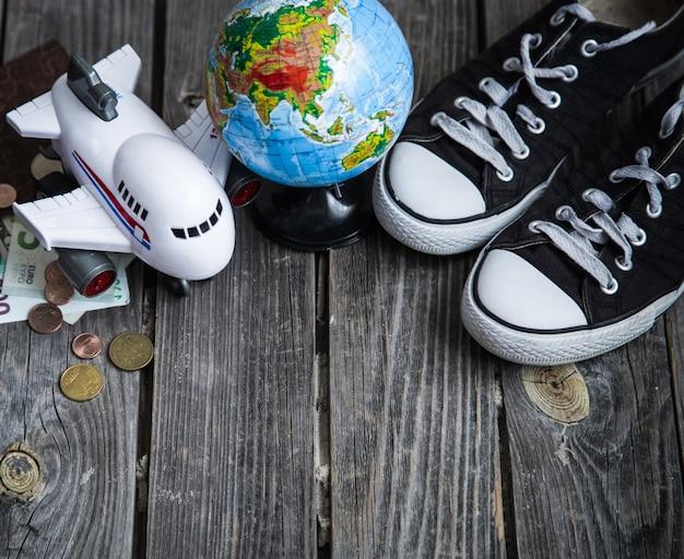 Sneakers, wereldbol en vliegtuig met geld Gratis Foto