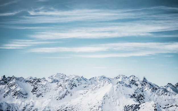 Sneeuwbergen onder een blauwe bewolkte hemel overdag Gratis Foto
