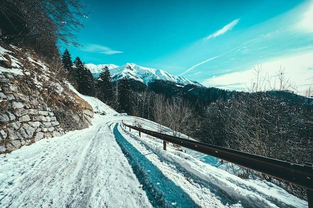 Sneeuwpad aan de zijkant van een berg met besneeuwde bergen Gratis Foto