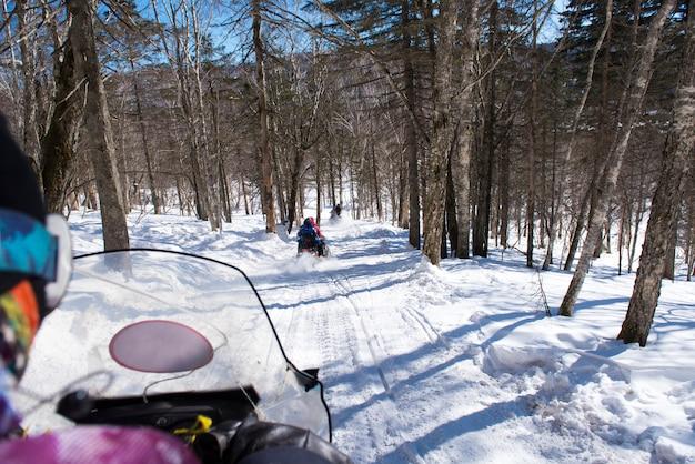 Sneeuwscooter in blizzard door het bos en het bos, openluchtsportconcept. Premium Foto