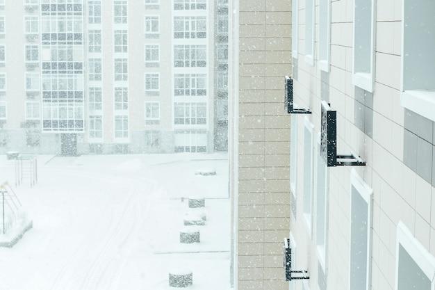 Sneeuwstorm in de stad. de tuin van een woongebouw is bedekt met sneeuw Premium Foto