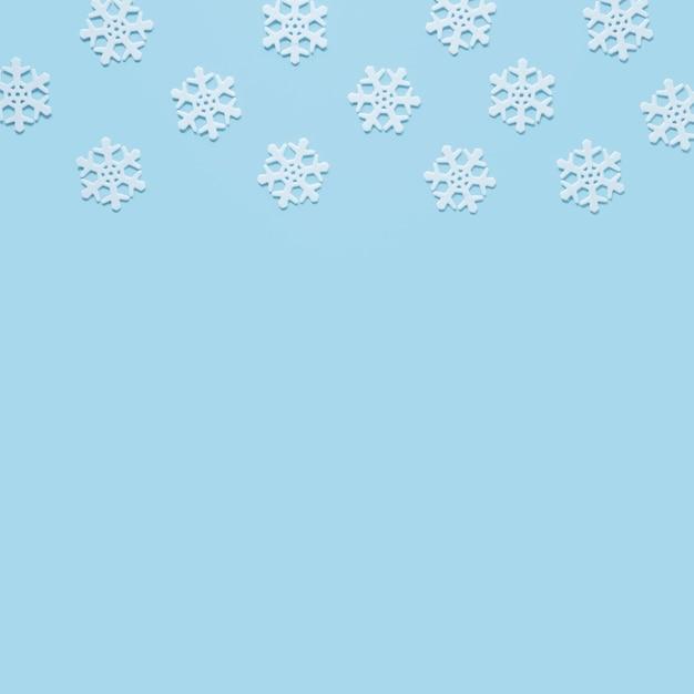 Sneeuwvlok op baby blauwe achtergrond met exemplaarruimte Gratis Foto