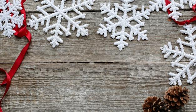 Sneeuwvlokken met dennenappels en rood lint Gratis Foto