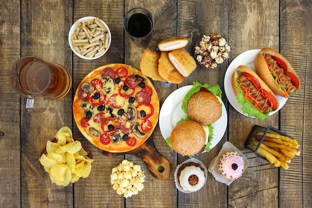 Snel voedsel op oude houten achtergrond Premium Foto