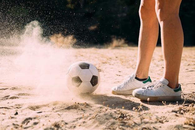 Snijd atletische benen aan die in openlucht door voetbal staan Gratis Foto